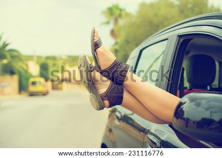 Woman's legs out of the car window. Vintage effect photo. - stock photo