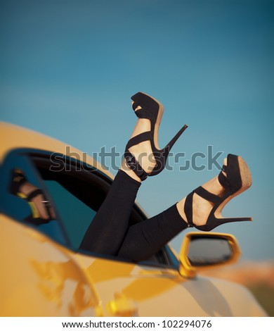 woman's legs with shoes by the way the car window on vacation. Concept of happiness and fun during the trip in the summer - stock photo