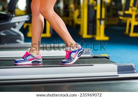 woman's muscular legs on treadmill, closeup - stock photo