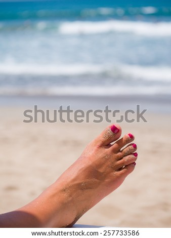 woman's sandy feet on the beach - stock photo