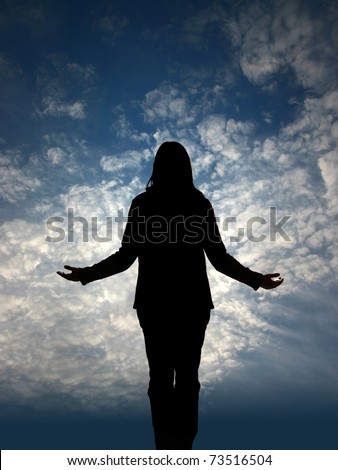 Woman`s silhouette on prayer in front of sky - stock photo