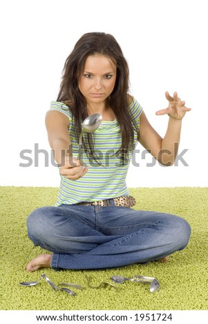 woman's sitting on the carpet bending spoon by mind force - stock photo