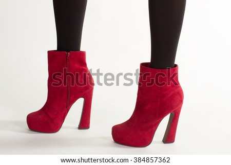 Woman's suede shoes. Close-up of bright footwear. Sexy legs in cherry ankle boots. Elegant suede ankle boots. - stock photo