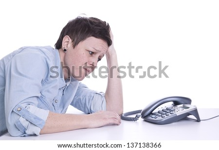 woman sat at a table, staring at a telephone, against white background, deciding whether to take or make a difficult phone call. - stock photo