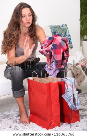 Woman sat on sofa looking through her shopping bags - stock photo