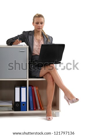 Woman sat with laptop on book case - stock photo