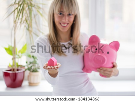 Woman saving money for her dream house - stock photo