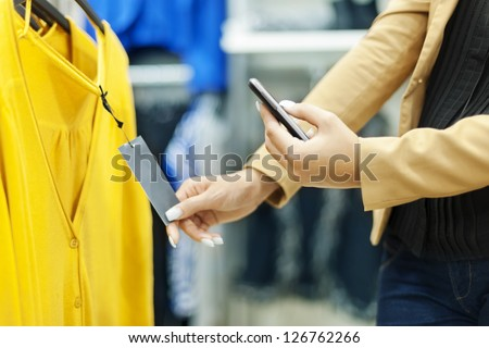 Woman scanning QR code in shopping mall - stock photo
