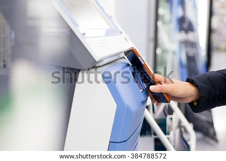 Woman scanning via mobile phone and machine - stock photo