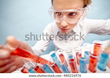 Woman scientist taking out tubing with red liquid