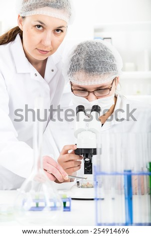 Woman scientist working with a microscope in a lab. - stock photo