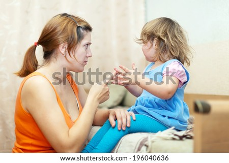 Woman scolds crying child at home interior