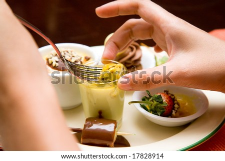 woman scooping her dessert from a cup on a plate with folk