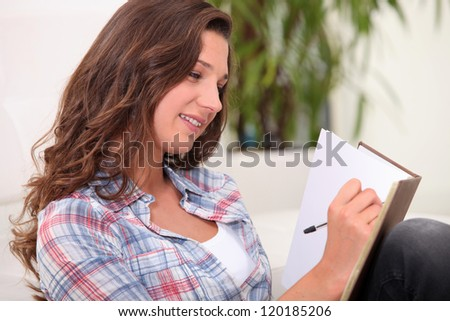 Woman scoring in notebook - stock photo