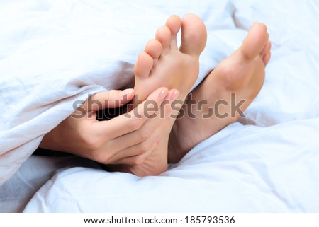 Woman scratches her foot - stock photo