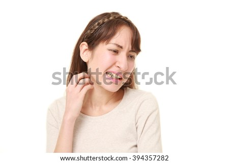 woman scratching her neck - stock photo