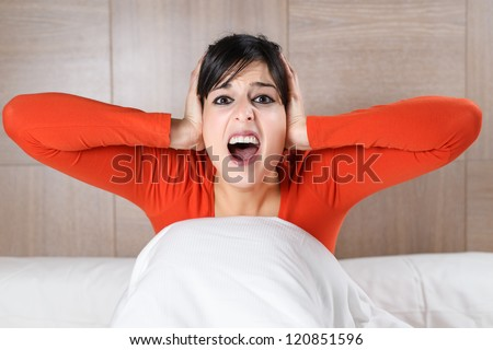 Woman screaming and covering ears on bedroom. Terrifying nightmares. Scared hispanic girl nightmare on bed. - stock photo