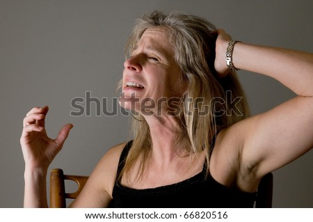 woman screaming and raging, suffering in pain and anger - stock photo