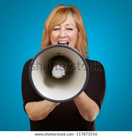 Woman screaming on a megaphone isolated on blue background - stock photo