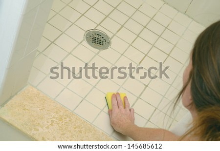 woman scrubbing soap scum from a dirty shower floor with scour pad - stock photo