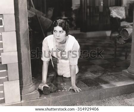 Woman scrubbing the floor - stock photo