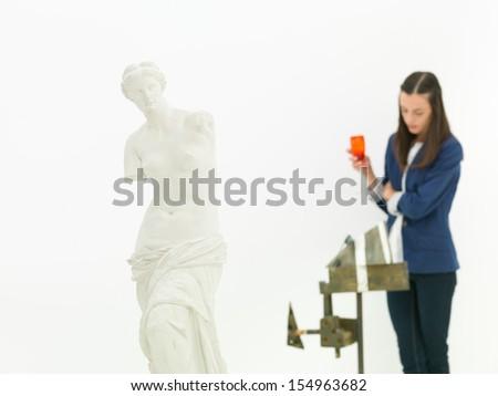 woman scrutinizing sculpture behind a replica of Venus de Milo statue in a museum - stock photo