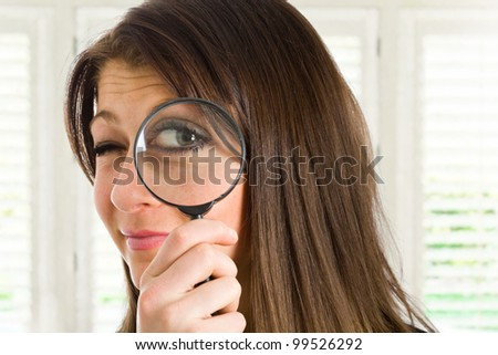 Woman searching for something using a magnifying glass - stock photo