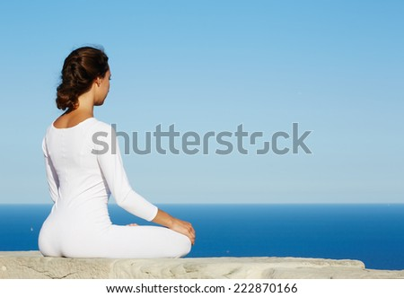 Woman seated in yoga pose on amazing ocean background, woman meditating yoga enjoying sunny evening, brunette woman makes yoga meditation sitting on mountain hill on amazing altitude, meditating woman - stock photo