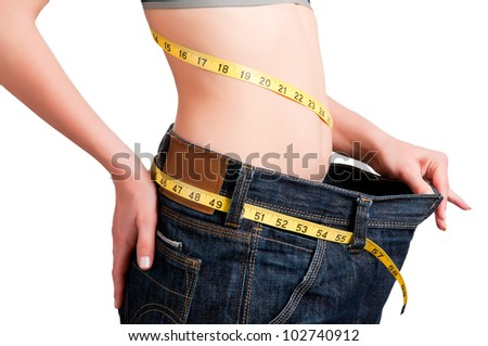 Woman seen how much weight she lost. Isolated background. - stock photo
