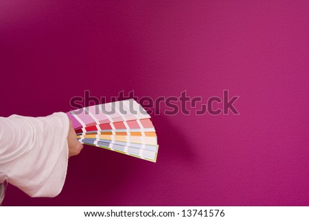 woman select a color to paint her wall - stock photo