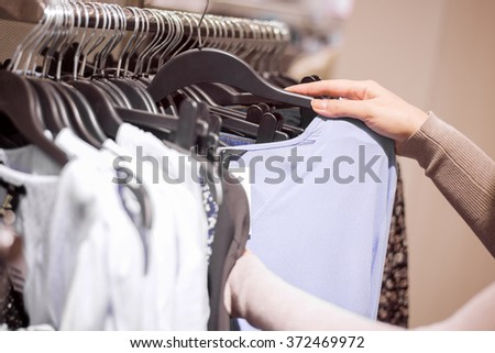 Woman selecting clothes in shop.Close up of hangers row. - stock photo