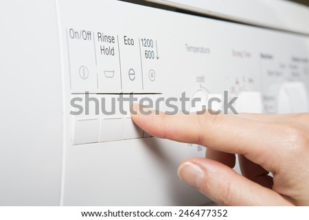 Woman Selecting Economy Program On Washing Machine To Save Energy - stock photo