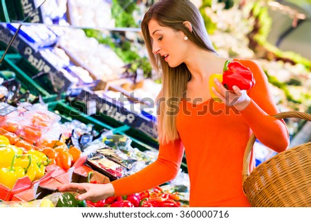 Woman selecting paprika while grocery shopping in supermarket  - stock photo