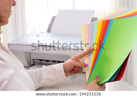 Woman selects color of paper for printer. - stock photo