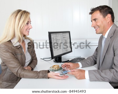 Woman selling gold to banker - stock photo