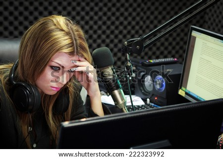Woman Serious And Moody While Working As DJ Radio Live Show In Studio - stock photo