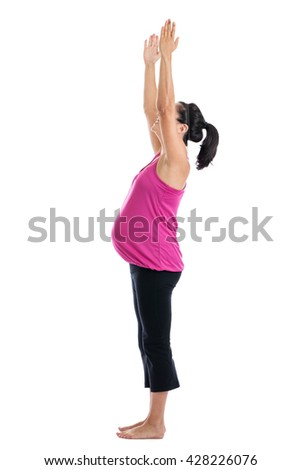 Woman seven months pregnant doing upward salute yoga stretch isolated on white - stock photo