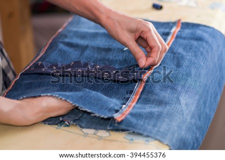 woman sewing denim. close-up on tools