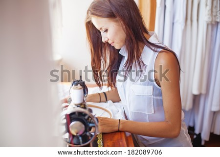 woman sewing on old sewing machine (focus on her eyes) - stock photo