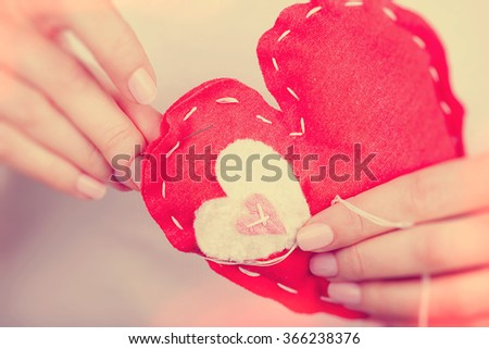 Woman sews red heart shaped toy by needle, body part, conceptual symbol of love and soul pain treatment, happy Valentine day - stock photo