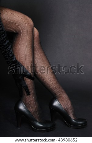 Woman sexy legs in shoes on black background - stock photo