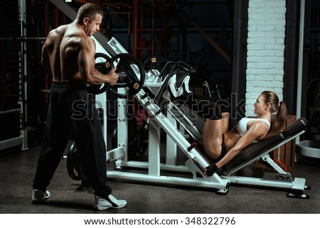 Woman shakes her legs over the bar. Man coach puts weight on the barbell. - stock photo