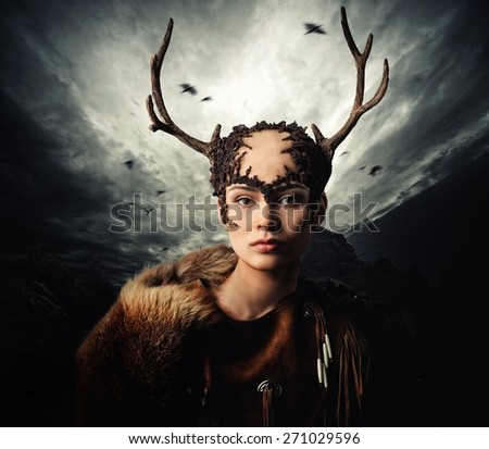 Woman shaman in ritual garment over dramatic stormy sky  - stock photo