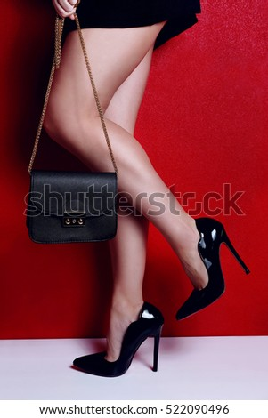 woman shapely legs wearing black lacquered high heel shoes with little black handbag. Close up view