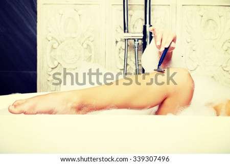 Woman shaving her leg with razor in bathroom.