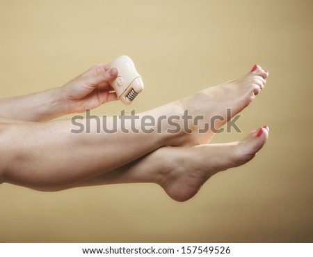 woman shaving her legs with electric shaver depilation body care on orange. Beauty and skin care concept. - stock photo