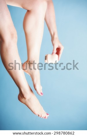 woman shaving her legs with electric shaver depilation on blue. Beauty and body skin care concept.