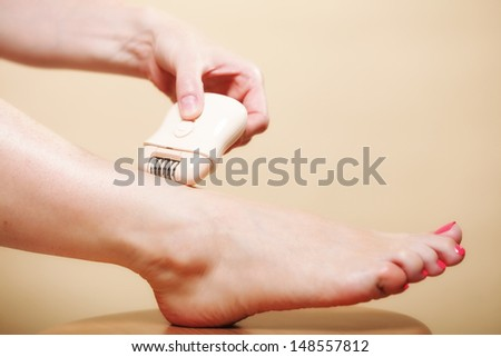 woman shaving her legs with electric shaver depilation on orange. Beauty and skin body care concept.