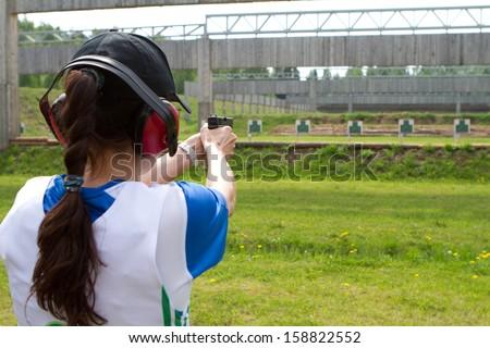 Woman shooting in shooting range - stock photo
