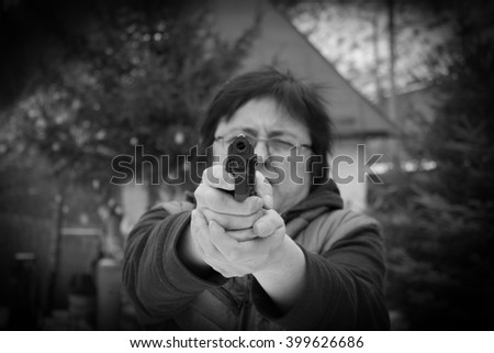 Woman shooting outdoor with a gun,  selective Focus on Pistol. - stock photo